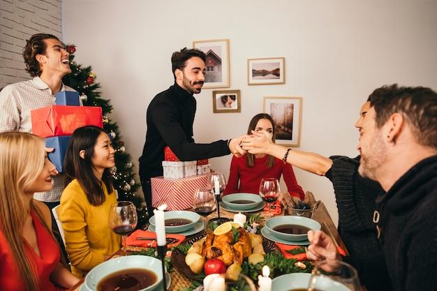 Groep van zes vrienden bij kerstmisdiner