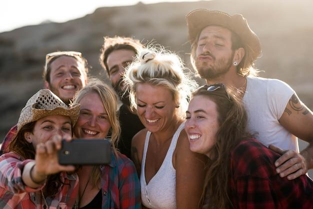 Groep van zeven mensen die samen een selfie maken, glimlachen en grappige gezichten kijken naar de camera van de telefoon