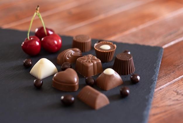 Groep verschillende chocolaatjes, melk en puur, op een zwarte achtergrond met rode kersen. houten tafel