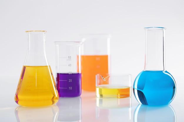 Groep verschillende kolven met kleurrijke vloeistoffen op een wit oppervlak in een lab