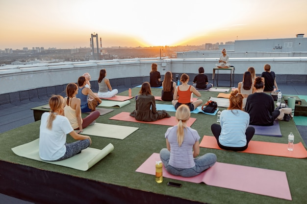 Groep verschillende mensen doen meditatieve yogapraktijken op het dak op een prachtige zonsondergang op zomeravond