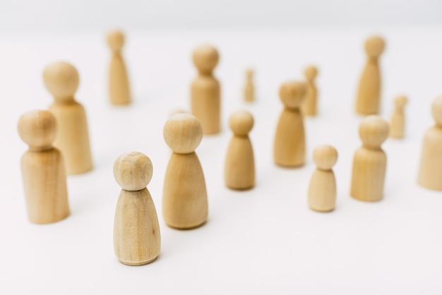Groep verwarde gegroepeerde mensen, vertegenwoordigd door houten figuren, geïsoleerd in studio op witte achtergrond.