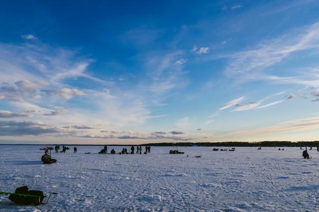 Groep vissers die in de winter op het ijs van de rivier vissen