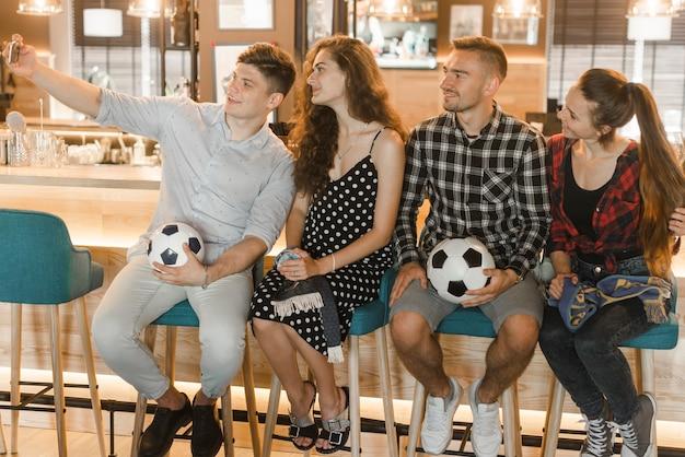 Groep voetbalfans die in bar zitten die selfie op slimme telefoon nemen