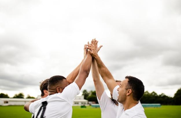 Groep voetballers die een hoogte vijf doen