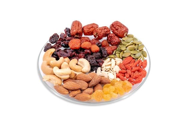 Groep volle granen en gedroogd fruit in een glasplaat geïsoleerd op een witte achtergrond.