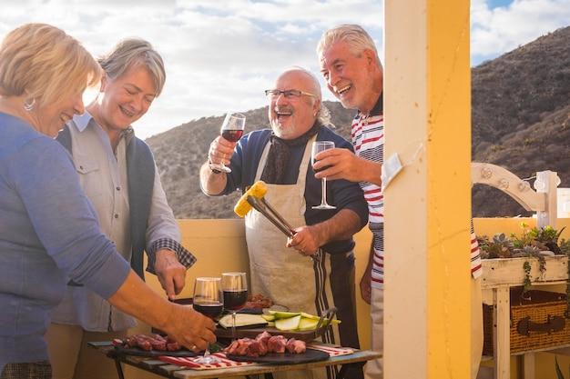 Groep volwassen blanke mensen genieten van de vriendschap samen eten en koken met barbecue buiten