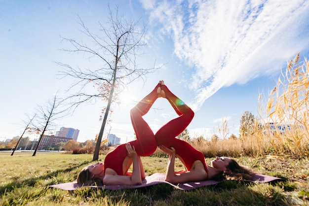 Groep volwassen kaukasische vrouw in sportieve kleren die een yogales buiten in park bijwoont. vrouwen die op gras in lotus-positie openlucht ontspannen zitten. kalmte en ontspanning, vrouwelijk geluk