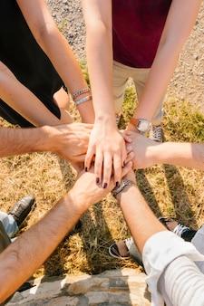 Groep volwassen vrienden die en handen zich verenigen bevinden