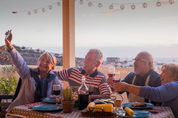 Groep volwassen vrienden ouderen gepensioneerd plezier maken van een foto zoals selfie allemaal samen tijdens een diner buiten op het dakterras vieren met maaltijd en wijn en herinneringen naar vrienden sturen