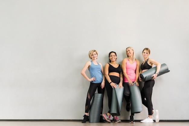 Groep volwassen vrouwen die bij de gymnastiek stellen