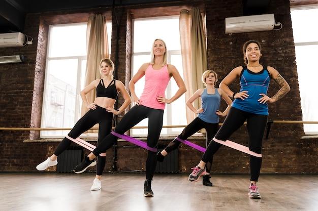 Groep volwassen vrouwen die bij de gymnastiek uitwerken
