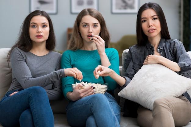 Groep volwassen vrouwen die op een film letten