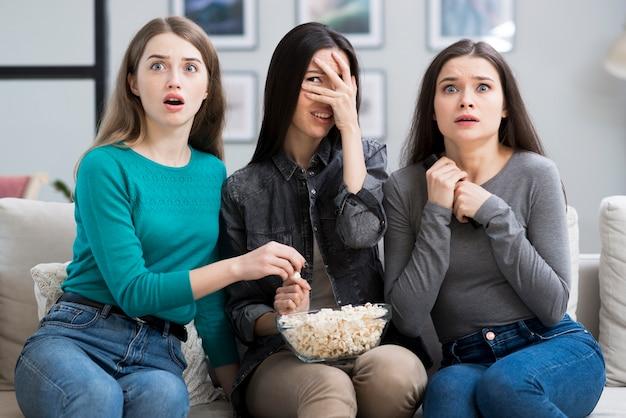 Groep volwassen vrouwen die op een griezelfilm letten