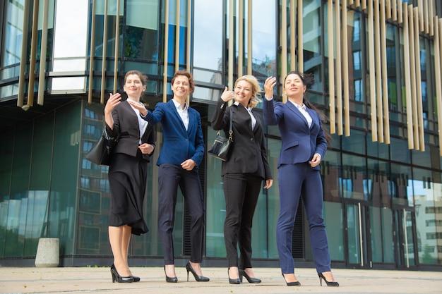 Groep vriendelijke bedrijfsvrouwen die handgebaar maken en iemand uitnodigen om zich bij team aan te sluiten. volledige lengte, vooraanzicht. we zijn aan het werven of welkom bij teamconcept