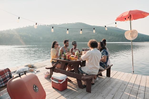 Groep vrienden aan tafel zitten en dineren op een pier met het prachtige landschap van het meer