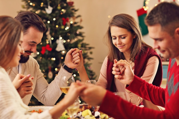 Groep vrienden bidden boven de kersttafel