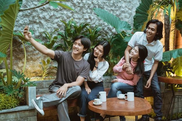 Groep vrienden bij de coffeeshop die samen een selfie maken