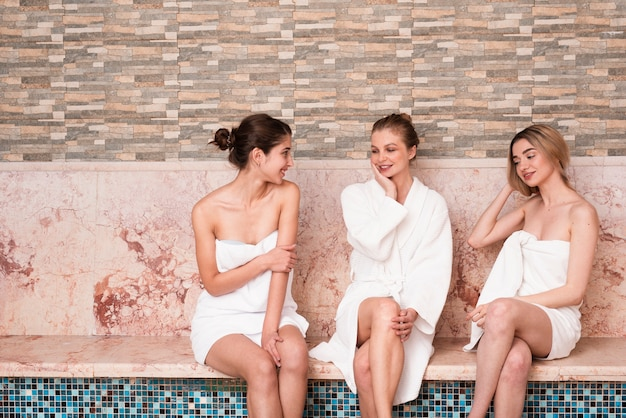 Groep vrienden chatten bij het zwembad in de spa