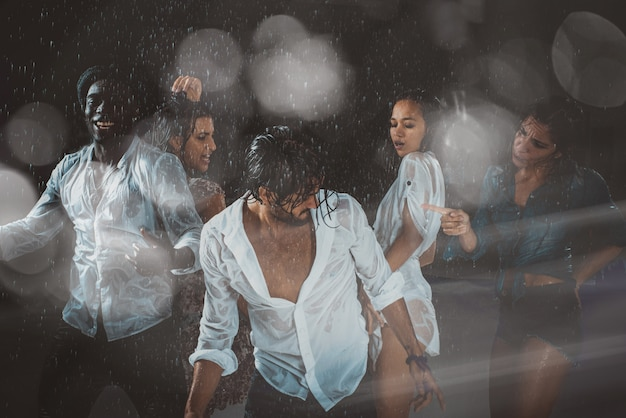 Groep vrienden dansen in de regen