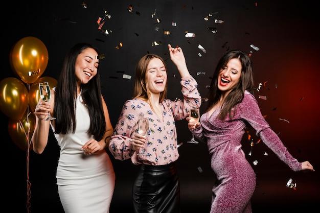 Groep vrienden dansen omringd door confetti