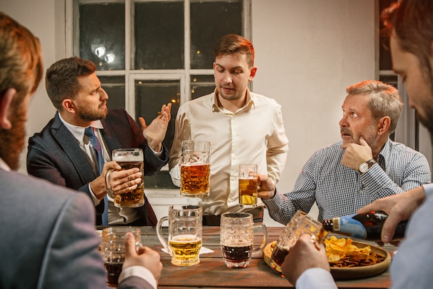 Groep vrienden die avond van dranken met bier op houten lijst genieten