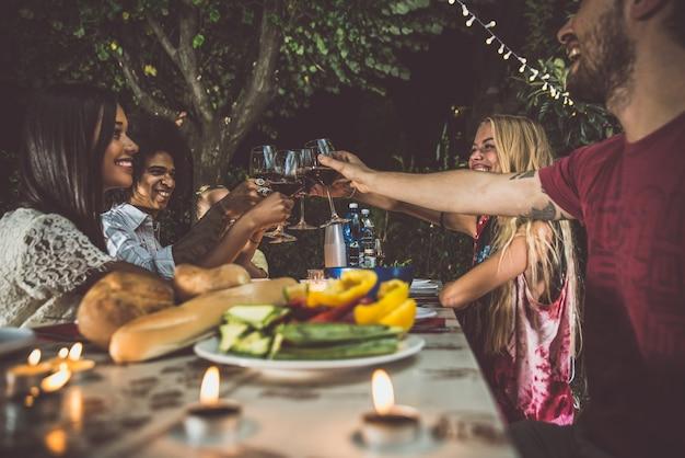 Groep vrienden die barbecue in de binnenplaats maken tijdens dinertijd