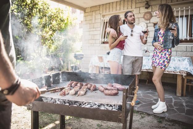 Groep vrienden die barbecue in de binnenplaats maken.