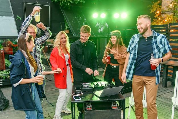 Groep vrienden die bier drinken, op de muziek dansen, babbelen en een goede rusttijd hebben op openlucht zomerfeest.