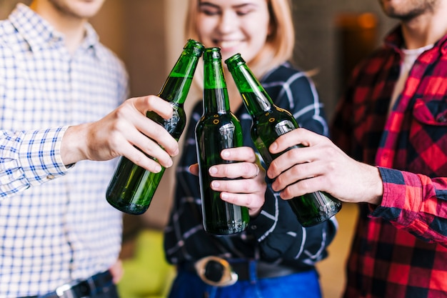 Groep vrienden die bierflessen in de bar rinkelen