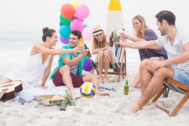Groep vrienden die bierflessen op het strand roosteren