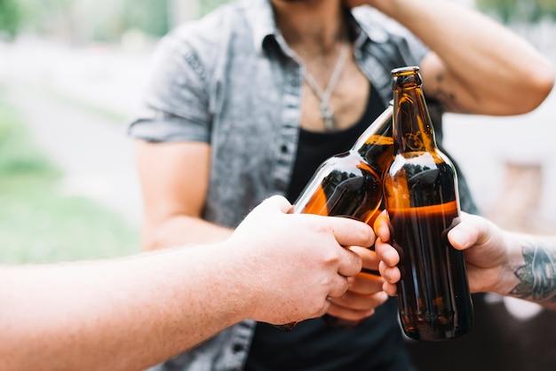 Groep vrienden die bierflessen roosteren bij openlucht
