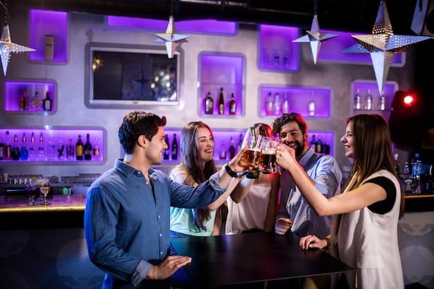 Groep vrienden die bierglazen roosteren bij barteller