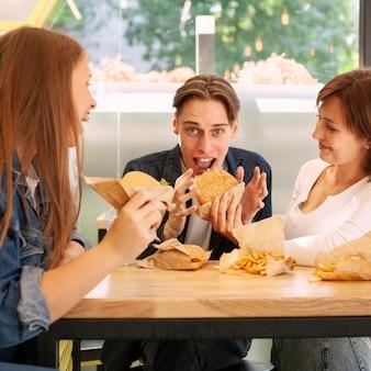 Groep vrienden die bij fastfoodrestaurant cheeseburgers eten