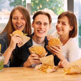 Groep vrienden die bij fastfoodrestaurant hamburgers eten