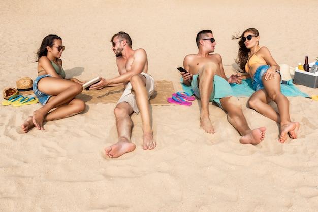 Groep vrienden die bij het strand liggen die een sunbath nemen
