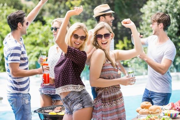 Groep vrienden die bij in openlucht barbecuepartij dansen