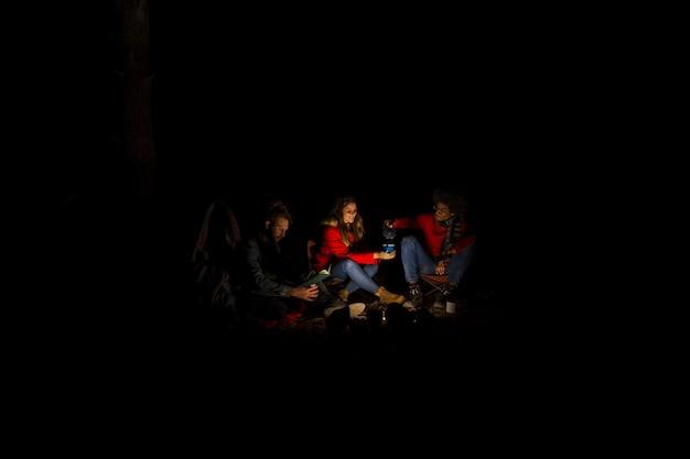 Groep vrienden die bij nacht kamperen