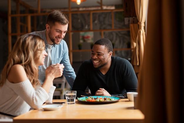 Groep vrienden die bij restaurant eten