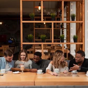 Groep vrienden die bij restaurant samenkomen
