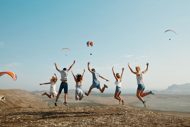 Groep vrienden die bovenop heuvel springen