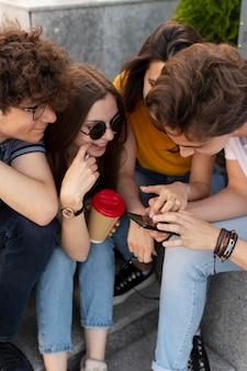 Groep vrienden die buiten in de stad koffie drinken en naar smartphone kijken