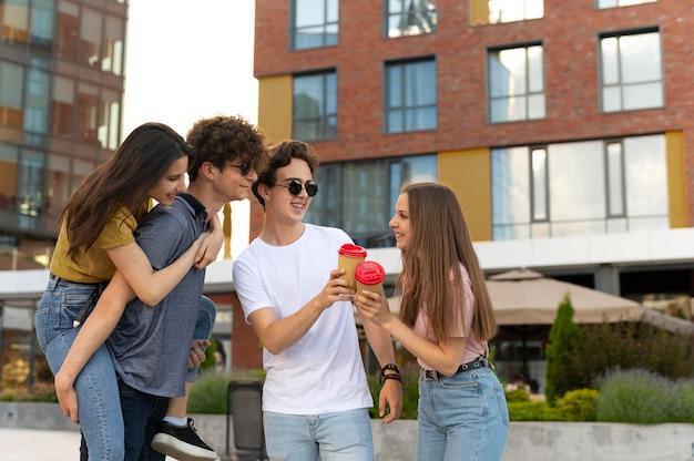 Groep vrienden die buiten koffie drinken in de stad