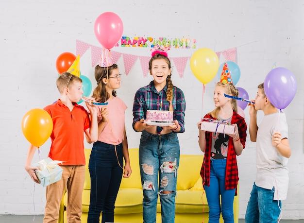 Groep vrienden die de cake van de meisjesholding verjaardag bekijken