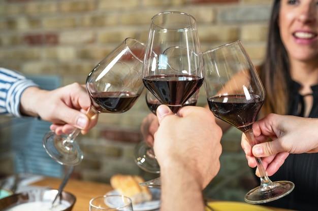 Groep vrienden die de glazen wijn houden die een toast maken.