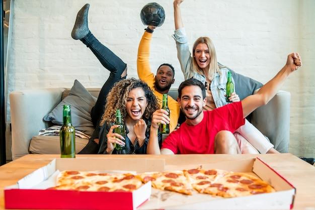 Groep vrienden die de overwinning vieren terwijl ze samen naar een wedstrijd kijken. vrienden en sport concept.
