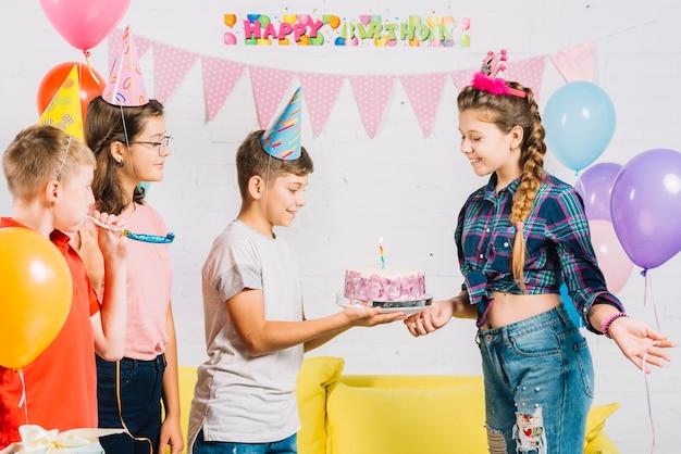 Groep vrienden die de verjaardag van het meisje met cake thuis vieren