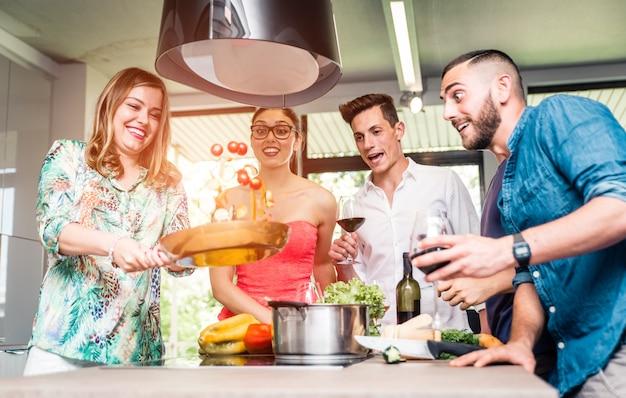 Groep vrienden die deegwarenpartij maken en pret in de keuken hebben