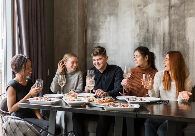 Groep vrienden die diner hebben samen thuis