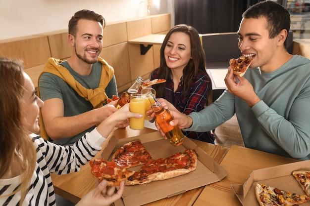 Groep vrienden die een leuk feest hebben met heerlijke pizza in café